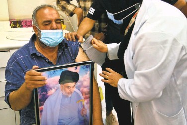 ?? Hadi Mizban / Associated Press ?? A follower of populist Shiite cleric Muqtada alSadr holds a picture of him while receiving the Chinese vaccine at a clinic in Baghdad. Hundreds of alSadr's followers are heading to clinics after he got the shot.
