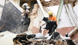 ?? | AP ?? A CHILEAN rescuer right, holds a rescue dog as they search among the rubble of a building that collapsed in last month's massive explosion in Beirut, Lebanon. Sniffer dog, Flash, indicated that there may be a survivor under the rubble.