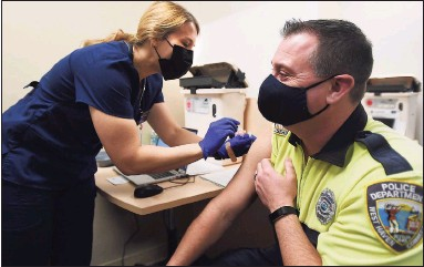 ?? Brian A. Pounds / Hearst Connecticut Media ?? West Haven police Officer Doug Bauman gets his Covid-19 vaccine at Griffin Health's vaccination center in Shelton on Feb. 16.