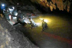 ?? —AP ?? WHATTODO Thai res­cuers en­ter the dark cave where 12 boys and their soc­cer coach have been trapped since June 23.