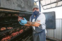 ??  ?? Tin Roof BBQ pitmaster William Tischina removes pork for hot meals.