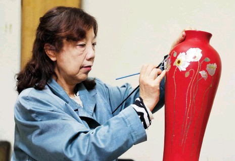 ??  ?? Yin Liping colors a lacquerware vase in Chengdu, Sichuan Province. — All photos by Xinhua
