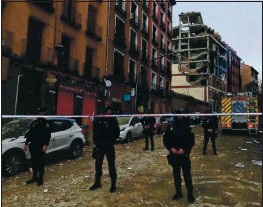 ?? BERNAT ARMANGUE — THE ASSOCIATED PRESS ?? Police officers cordon off Toledo Street following an explosion in downtown Madrid, Spain, on Wednesday that killed four people.