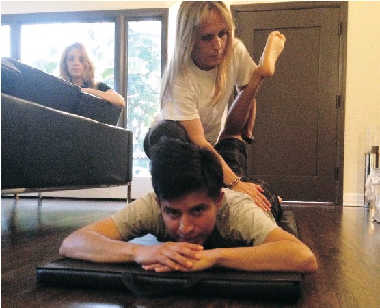 ?? DENISE RYAN ?? Jockey Mario Gutierrez works on stretching with fitness coach Sabrina Perruzi as his wife Rebecca looks on in their home. He's now in the top 10 in U.S. jockey rankings.