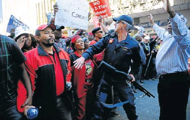 ?? Pictures: SAPA ?? CONFRONTATIONAL: A policeman tries to control a tense situation between a violent Cosatu crowd and Democratic Alliance supporters in Johannesburg yesterday. DA members were participating in their youth wage subsidy march