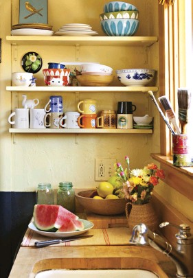 """??  ?? TRISH'S DISHES are all eclectic vintage pieces, bringing refreshing variety to everyday life. She muses over her mugs, """"Which one of them am I going to choose today?"""" In a bold move that added a chic touch to the kitchen, Trish painted the bottom half of the walls black."""