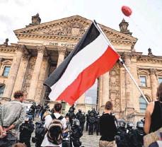 ?? FOTO: SOMMER/DPA ?? Teilnehmer einer Kundgebung gegen die Corona-maßnahmen stehen im August 2020 vor dem Reichstag in Berlin, ein Teilnehmer hält eine Reichsfahne. Jetzt wollen die Innenminister geschlossen gegen den Missbrauch der Fahnen vorgehen.