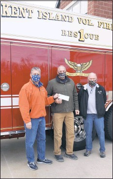 ?? KIVFD ?? Mitchell Andrew (left) and Wheeler Baker (right) present a year end donation to Kent Island Volunteer Fire Department President, Jody Schulz.