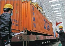 ?? CAI ZENGLE / FOR CHINA DAILY ?? Workers transfer containers from an inbound train to a domestic train at the Alashankou Port, Xinjiang Uygur autonomous region, in September.