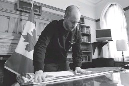 ?? SEAN KILPATRICK/THE CANADIAN PRESS ?? Flag master Robert Labonté, who takes care of the flags that fly on Parliament Hill, folds one of the flags in Ottawa on Thursday.