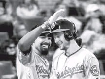 ?? TANNEN MAURY/EPA-EFE/SHUTTERSTOCK ?? Trea Turner, who also doubled and tripled in Washington's 16-hit attack, is greeted by Anthony Rendon after a fifth-inning homer.