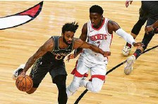 ?? Matt Marton / Associated Press ?? Bulls guard Coby White, left, drives with new Rockets guard Victor Oladipo defending during the first half Monday.