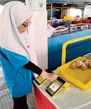 ?? PIC COURTESY OF EMERGING ENTERPRISE SDN BHD ?? A student making a cashless transaction at a school canteen in Kuala Lumpur recently.