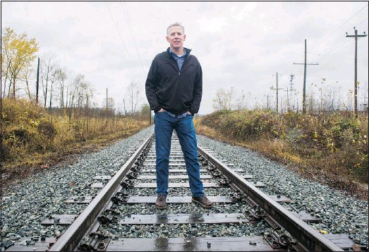 ?? GERRY KAHRMANN/PNG ?? Pastor Jim Heuving stands on the railway tracks near Pacific Community Church. He calls the tracks the 'homeless highway' because impoverished people in the area use them to get back and forth.