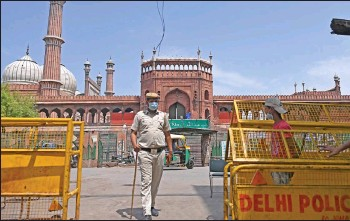 ??  ?? Police stand guard in the backdrop of the Jama Masjid mosque as a lockdown is in effect wherein only people catering to essential services were allowed to commute as directed by the Delhi state government to curb the spread of the Covid-19 coronavirus infections in New Delhi. — AFP photo