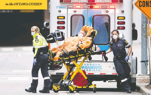 ?? PETER J THOMPSON / NATIONAL POST ?? Paramedics take a patient into St. Michael's Hospital in Toronto on Tuesday, as facilities across Canada prepare for an expected surge in coronaviru­s patients.
