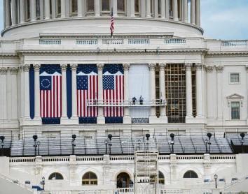 ?? Foto: Liu Jie, dpa ?? Die Flaggen zur Amtseinführung des gewählten US‰Präsidenten Joe Biden hängen bereits am Kapitol. Doch so etwas wie Feier‰ lichkeit will nicht aufkommen. Im Gegenteil, die Furcht vor erneuten Ausschreitungen wächst.