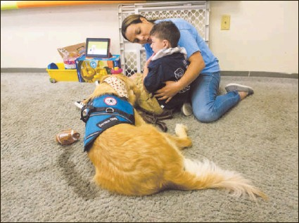 ?? DAVID MCKEOWN / STAFF PHOTOGRAPHER ?? Jansell Nunez holds her son, Dariel Nunez, as they sit with his new service dog, Kluck, on Thursday at St. Joseph's Center for Special Learning, Pottsville.