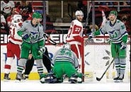 ?? KARL B DEBLAKER   Associated Press ?? The Wings celebrate a goal, and the Hurricanes, in the franchise's Hartford Whalers uniforms, pause and reflect. Wild.