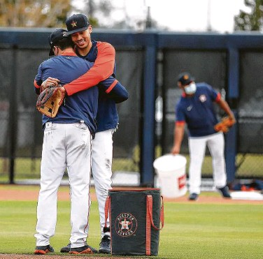 ?? Photos by Karen Warren / Staff photographer ?? Star shortstop Carlos Correa, whose voice will carry the most weight in the Astros' clubhouse, hugs hitting coach Troy Snitker during Monday's first full-squad spring training workout for the team in Florida.