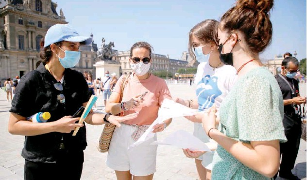 ?? Reuters ?? ↑ A security agent checks visitors' health passes in front of the Louvre museum in Paris on Wednesday.