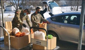 ?? PHOTOS BY CRYSTAL BEAULIEU — THE NEWS-HERALD ?? Fresh produce, canned goods, meat and dairy are loaded into cars at Vineyard Community Church by the National Guard.