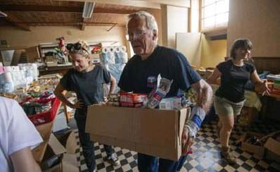 ??  ?? Vrijwilligers brengen in Pepinster dozen met hulpgoederen naar de zwaarst getroffen gezinnen.