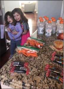 ?? SUBMITTED PHOTO ?? Noelle Stahl, right, and her sister Claire, with some of the snacks they prepared and donated.