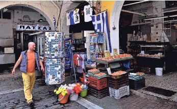 ?? SAKIS MITROLIDIS, AFP/GETTY IMAGES ?? A man passes a market in Tessaloniki on Tuesday. Greece's Prime Minister Alexis Tsipras on Sunday blasted creditors for insisting on what he called absurd changes that have held up talks.