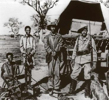 ?? FOTO: ULLSTEIN BILD ?? Deutsche Kolonialpolitik und Herero-Aufstand in Deutsch-Südwestafrika: Gefangene Hereros in Ketten werden von einem Soldaten der Schutztruppe mit Gewehr und aufgepflanztem Bajonett bewacht (1904).