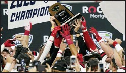 ?? CARLOS OSORIO — THE ASSOCIATED PRESS ?? Ball State players reach for the trophy after defeating Buffalo in the MidAmerican Conference championship on Friday in Detroit.