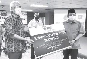 ?? — Gambar Bernama ?? BANTU: Mahdzir (kiri) menyampaikan replika cek sumbangan bantuan kelengkapan sekolah kepada pelajar sekolah di Parlimen Machang kepada Ahmad Jazlan (kanan) pada Majlis Program Ceria Ke Sekolah TNB di Kota Bharu semalam.