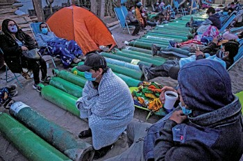?? — AFP file photo ?? People camp as they wait to refill empty oxygen cylinders in Villa el salvador, on the southern outskirts of Lima, amid the Covid-19 coronavirus pandemic.