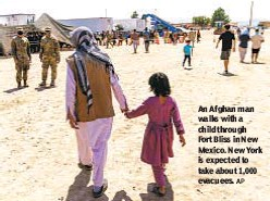 ?? AP ?? An Afghan man walks with a child through Fort Bliss in New Mexico. New York is expected to take about 1,000 evacuees.