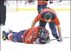 ?? Nick Wass/Associated Press ?? Washington left winger Alex Ovechkin is tended to by a trainer after being injured in the first period against Toronto.