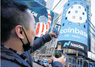 ?? Photo /AP ?? Coinbase employee Daniel Huynh celebrates with a bottle of champagne in New York's Times Square.