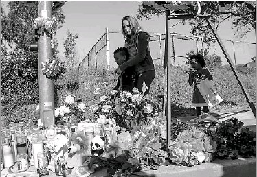 ?? Irfan Khan/Los Angeles Times ?? Emily Swayer, 26, and her children Trayvon (left), 7, and Honey, 4, paid their respects Tuesday at a makeshift memorial for the victims of the shooting at North Park Elementary in San Bernardino, Calif.
