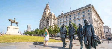 ?? Associated Perss ?? ↑ A woman walks past The Beatles statues and Royal Liver Building on the waterfront area of Liverpool on Wednesday.