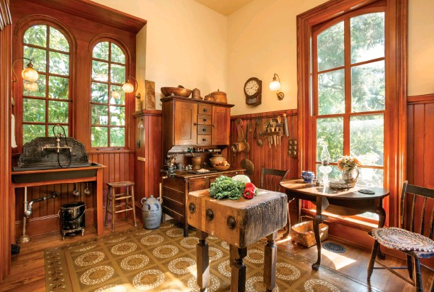 ??  ?? REPRODUCTIONS OF THE 1861 WINDOWS TIE THE KITCHEN ADDITION TO THE ORIGINAL HOUSE. A HAND-PAINTED FLOORCLOTH, FOUND ON E-BAY, PROTECTS THE KITCHEN'S WOOD FLOORS. AN OLD BUTCHER BLOCK ACTS AS A PREP ISLAND, AND AN EARLY HOOSIER CABINET IN ITS ORIGINAL...