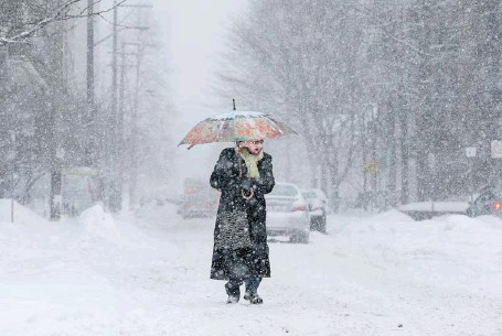 ?? JULIE OLIVER/OTTAWA CITIZEN ?? Sidney Hicks tries to fend off the snow with her umbrella while having to take the middle of the street to walk downtown.