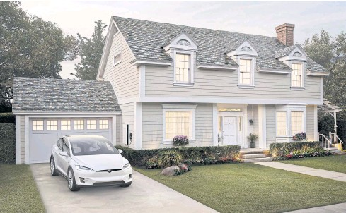 ?? TESLA INC VIA AP ?? This photo provided by Tesla Inc shows a house with the company's new slate solar roof tiles.