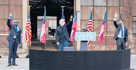 ?? PATRICKSEMANSKY/AP ?? President-elect Joe Biden, center, acknowledges supporters at a rally last month for Georgia Democratic candidates for U.S. Senate Raphael Warnock, left, and Jon Ossoff in Atlanta.