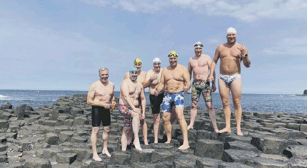 ??  ?? 0 From left, Adrian Poucher (support crew), Dominic Mudge, Keith Garry, John Mcelroy, Bill Donnelly, Colin Lindsay and Chris Judge on the Giant's Causeway after completing their swim from Islay