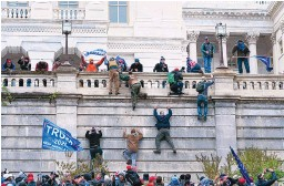 ?? JOSE LUIS MAGANA/ASSOCIATED PRESS ?? Supporters of President Donald Trump climb the west wall of the U.S. Capitol in Washington on Jan. 6. Court documents filed Tuesday allege that three defendants planned an attack and communicated by radio while it went on.