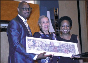 """?? PHOTO BY DUSTIN HOLT ?? Civil rights leader Gloria Richardson Dandridge, center, receives a print of the Cambridge mural celebrating the city's African-American history during the Reflections on Pine Gala Friday, July 21, in Cambridge. Dandridge was presented the mural print by Eastern Shore Network for Change founders and """"Reflections on Pine"""" organizers Dion Banks and Kisha Petticolas."""