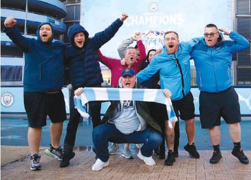 ??  ?? Manchester City fans celebrate their club winning the Premier League title outside the Etihad Stadium in Manchester on Tuesday. Reuters