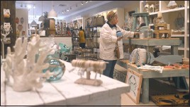 ??  ?? One of the first shoppers in line at the opening looks through the coastal country offerings of Farm Charm in the Queenstown Premium Outlets. Coral, crabs and sailboats are all on display.