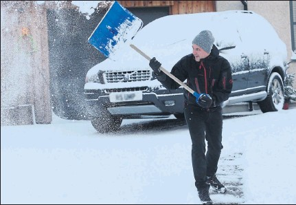 ??  ?? GIFT FROM CONOR: Scott Burns-Smith clears snow from his driveway near Inverness after the latest storm hit travel plans. Picture: Peter Jolly
