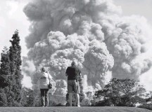 ?? TERRAY SYLVESTER/REUTERS ?? People watch ash erupt from the Halemaumau Crater near the community of Volcano on the Big Island on May 19.