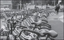 ?? WANG QIMING / FOR CHINA DAILY ?? A rider parks a shared bicycle at a parking lot earmarked for shared bikes in Nanjing, Jiangsu province, in October.